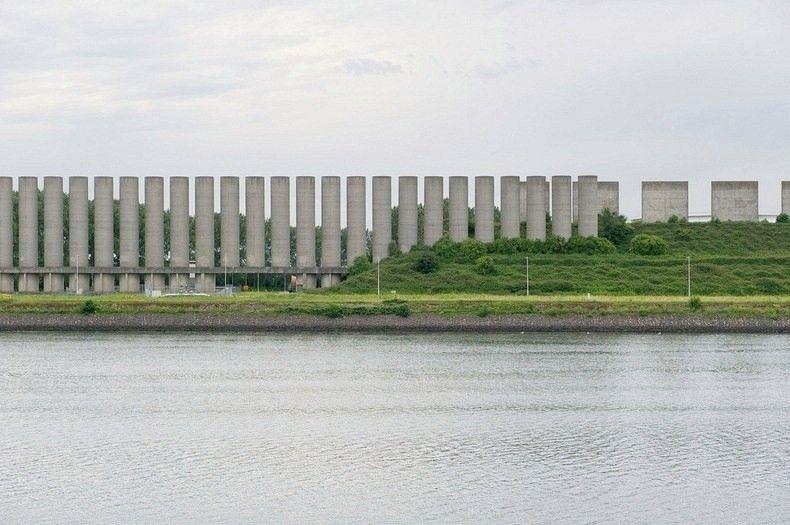 Ветровая стена РозенбургаРозенбург – маленький портовый город и бывший муниципалитет на западе Нидерландов, в провинции Южная Голландия. Чтобы совладать с растущим морским грузооборотом, в конце 1960-х годов был построен новый судоходный канал. Однако с увеличением размеров судов, широкий канал вскоре стал неудобным для передвижения по нему во время сильных ветров, в частности неподалёку от моста Каландбруг.В середине 1980-х годов архитектор Мартин Струйис получил задание создать эффективный и в то же время хорошо выглядящий ветрозащитный барьер. Результатом работы стала Ветровая стена Розенбурга.Сооружение выглядит, как крупномасштабная инсталляция ландшафтного дизайна и состоит из 125 отдельных бетонных плит, установленных и изготовленных по определённому шаблону. Они занимают 1,75 километров в длину, и снижают силу ветра на 75%. В южной части канала плиты выполнены в форме полукругов – 18 метров в ширину и 25 метров в длину. Однако ближе к мосту Каландбруг обхваты полукруглых образований Ветровой стены снижаются, и каждая стена располагается ближе к остальным.Около моста ширина стен достигает всего 4 метров. На севере стены полукруглые плиты сменяются кубическими плитами размером в 10 метров, которые расположены на насыпи высотой в 15 метров, что в целом позволяет достичь тех же 25 метров, как и в других секциях. Барьер сохраняет эту форму до самого конца, где среди деревьев расположено газохранилище.#история #инженерные_сооружения #нидерланды