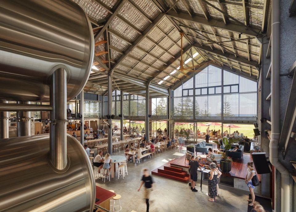 """Пивоварня Shelter Brewery в АвстралииПроект пивоваренного завода с экскурсионным залом и рестораном Shelter Brewery разработан бюро Paul Burnham Architect и реализован в 2020 году в городе Басселтон в Западной Австралии.Особенность проекта - расположение смотровых площадок и ресторана непосредственно вокруг производственного ядра комплекса, открытого для обозрения. Емкостное оборудование пивоварни, выполненное из нержавеющей стали, одновременно является и главной достопримечательностью зала.Здание со стальным каркасом, облицованное стеклом и ржавым кортеном, идеально сочетается с его промышленным содержимым. В девятнадцатом веке на этом участке также располагались производственные комплексы - объекты китобойного промысла и пакгаузы компаний, торгующих сандаловым деревом. Высокий """"ангарный"""" профиль здания служит отсылкой к архитектуре той эпохи.В проекте в значительной степени реализован потенциал географического расположения объекта. Крыша пивоварни полностью покрыта солнечными панелями, которые, по информации разработчиков проекта, обеспечивают примерно 80% потребностей завода в электроэнергии. При проектировании вентиляции учтено влияние морского бриза, что позволило значительно снизить энергетические нагрузки.#промышленныездания #австралия"""