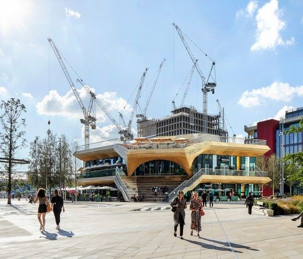 """В Лондоне реализован проект архитектурного бюро ACME, """"The Pavilion"""", представляющий собой вертикальное общественное пространство. Сооружение, решенное в деревянном каркасе, состоит из трех этажей, на которых расположены множество пабов, кафе, ресторанов и общественных залов.Сооружение предназначено для встреч и общения людей, а также проведения общественных мероприятий. Оно организовано как многоуровневая городская площадь, с которой обеспечивается доступ ко всем ключевым точкам района Стратфорд-Сити, в том числе, к Олимпийскому парку королевы Елизаветы и Восточному берегу (East Bank).Фасад здания также выполняет роль общественного пространства: он решен в виде множества лестниц, балконов и амфитеатров, удобных для времяпрепровождения. На крыше """"Павильона"""" организована общественная терраса с видом на парк.Выбор дерева для строительства в данном случае обусловлен не только экологическими соображениями, но и расчетом нагрузок. Здание расположено над тоннелем линии Доклендс (DLR) и возможные нагрузки были значительно ограничены при разработке проекта. Поэтому каркас и частично фасад выполнены из легких деревянных конструкций.#деревянныеконструкции #общественныездания #великобритания"""