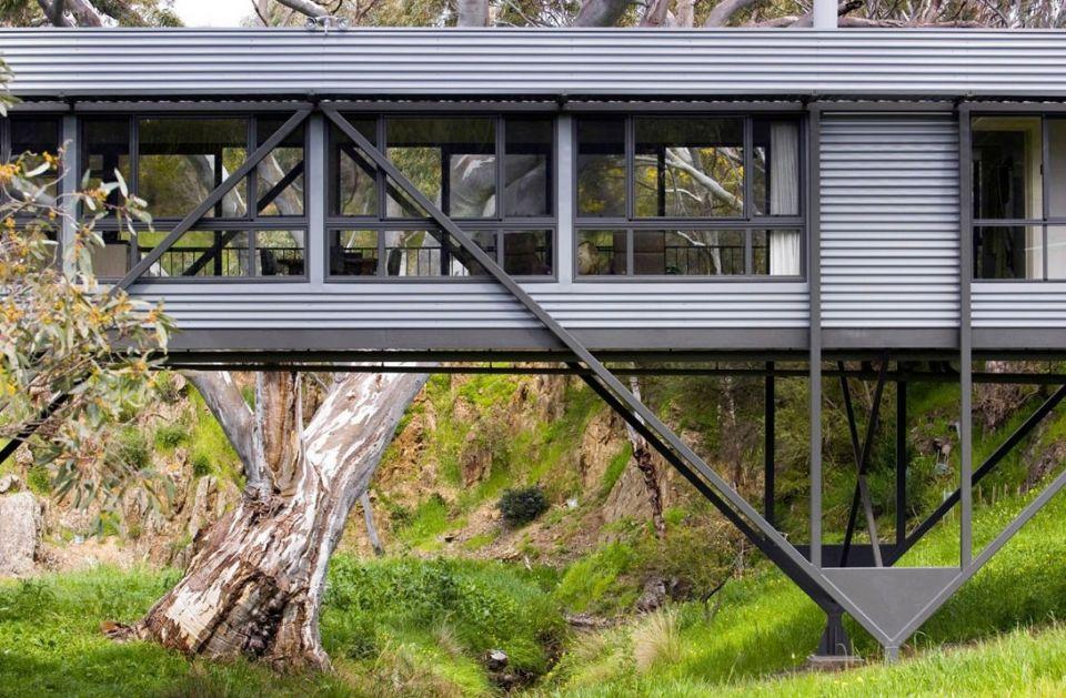 Bridge House - дом-мост в АвстралииЖилой дом по проекту Max Pritchard Architect возведен на сложном рельефе участка, расположенного в часе езды от города Аделаида (Австралия). Так как небольшой участок земли оказался разделенным пополам руслом сезонного ручья, разработчики проекта предложили вариант строительства здания-моста, соединяющего два берега. Такое решение позволило не только значительно удешевить строительство, но и сохранить природный ландшафт местности и растительность.Основные несущие конструкции здания выполнены из двух стальных ферм, опирающихся на небольшие столбчатые железобетонные фундаменты. В качестве пола использована железобетонная плита. Стены и покрытие - из деревянных плит.В здании не используется кондиционирование воздуха. Внутренний климат обеспечивается комбинацией естественной и принудительной вентиляции, эффективной теплоизоляции ограждающих конструкций, а также затенением фасадов. Здание оборудовано системой сбора дождевой воды, локальными очистными сооружениями и солнечным нагревателем воды.#малоэтажноестроительство #мосты #австралия