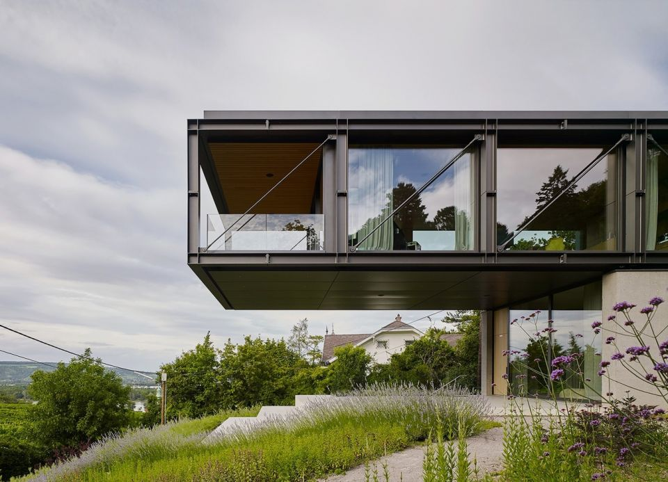 Консольный дом на склоне в АвстрииИнтересный проект частного дома реализован в Вене в 2018 году. Здание площадью 335 м2 построено на крутом склоне на виноградниках, на окраине Вены.Верхний уровень здания решен в стальном каркасе. Длина боковых ферм составляет 36 метров, двенадцать из которых простираются над склоном в виде консоли. Из панорамных окон открываются потрясающие виды на окружающие горы и Дунай.Здание имеет четыре этажа, один из которых полностью наземный, а еще три - утоплены в склоне. В отличие от верхнего этажа, три нижних уровня выполнены из монолитного железобетона. Доступ на этажи осуществляется через лестницу и лифт.Вход с улицы организован на нижнем этаже, где расположен гараж. Второй этаж занимают технические и подсобные помещения. На верхних уровнях расположены спальни, детская, гостевые комнаты и общий зал с камином. В интерьерах помещений преобладает отделка дубом, что усиливает ощущение связи с окружающим природным ландшафтом.#консоли #малоэтажноестроительство #австрия