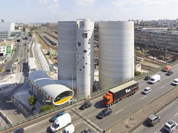 Склад цемента в ПарижеНа юго-восточной окраине Парижа (13 округ) в мае 2014 года было завершено строительство цементного склада настолько необычного и запоминающегося облика, что он стал архитектурной доминантой всего района Bruneseau Nord (Paris Rive Gauche).Заказчиком проекта выступил концерн Ciments Calcia, а исполнителем – парижская студия Vib Аrchitecture, генеральным подрядчиком стала компания Semapa.Грамотный выбор расположения цементного склада определил себестоимость перевозок на десятки лет вперед. Участок площадью около 0,5 га расположен вплотную с сортировочной станцией вокзала Аустерлиц, обеспечивающей ж.д. доставку цемента, и буквально в 5 метрах от юго-восточной дуги кольцевой столичной автострады с пропускной способностью 300 тыс. транспортных средств в сутки. С вводом в эксплуатацию до 80% клиентов заказчика проекта находятся в пределах 30 км зоны вокруг цементного склада.Кроме силосов комплекс включает в себя башню обслуживания с лифтом, а также лабораторно-технологический (180 м2) и административный корпус (150 м2). Оба корпуса выполнены в виде овальных туннелей. Причем лабораторный корпус расположился на обычном фундаменте, а административный, как ему и полагается, поднят на пилонах в своей ракушке (термин – авторов проекта) до уровня европейской автострады. Форма административного здания плавно огибает один из бункеров. Такой конструкцией авторы проекта стремились продемонстрировать пластические возможности современного железобетона.