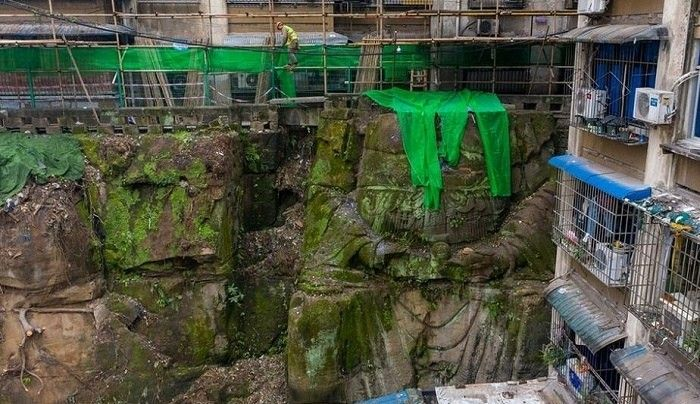"""В Китае статуя Будды более 40 лет использовалась в качестве подпорной стены многоэтажного жилого зданияВ китайском городе Чунцин во время подготовительных работ для реконструкции многоэтажных жилых зданий внезапно оказалось, что одно из них частично опирается 9-метровую статую Будды. По предварительной информации, озвученной изданием South China Morning Post, жилые здания были построены в 80-х годах на месте старого буддийского храма.Сам храм был снесен, а статуя Будды была использована в качестве части подпорной стены, и новое здание было построено непосредственно над ней. При этом голова статуи была демонтирована.Со временем статую покрыли дикие вьющиеся растения и мусор, и новое поколение жильцов даже не знало, что их дом стоит на статуе. Во время подготовительных работ к реконструкции здания, растения и мусор были удалены, и забытую статую таким образом «откопали». Некоторые старожилы вспомнили и рассказали о том, как велось строительство.В настоящее время на площадке работают специалисты. Инженеры должны дать оценку необычному """"техническому решению"""" и степени его безопасности, а археологи должны определить возраст статуи и ее историческую ценность.#история #китай"""