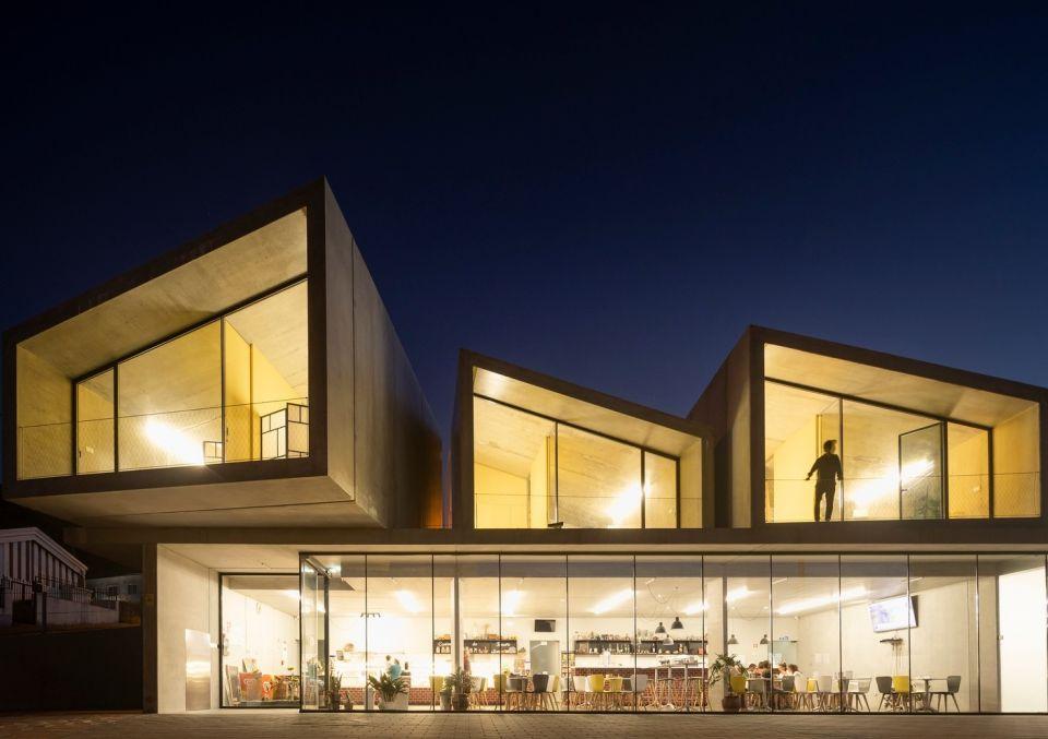 Модульные жилые здания в Португалии по проекту SummarySummary - португальское архитектурное бюро, уже много лет специализирующееся на разработке и внедрении модульных строительных систем. Один из последних реализованных проектов студии - малоэтажный жилой и коммерческий комплекс в городе Вали-ди-Камбра. Выбор модульных зданий был определен исходя из задачи проекта - строительство должно было быть быстрым, экономически эффективным, с возможностью легкой реконструкции и изменения через некоторое время.Здание состоит из двух частей: коммерческий центр из сборных элементов на первом этаже и индивидуальные жилые блоки на втором (шесть модулей по 45м2). Как первый, так и второй этажи могут легко наращиваться и расширяться при необходимости.Блоки изготавливаются на заводе из железобетона с теплоизоляцией и не требуют никакой дополнительной отделки. По мнению архитекторов, такая префабрикация - это неизбежный процесс, вытекающий из демографических проблем и растущего дефицита рабочей силы. Именно за такими технологиями - будущее.В своих технических решениях студия использует опыт крупнопанельного домостроения, распространенного в середине прошлого века в СССР, ГДР, Франции и других странах, переосмысливая его с учетом современных потребностей людей и трендов строительного рынка.#малоэтажноестроительство #модульныездания #португалия