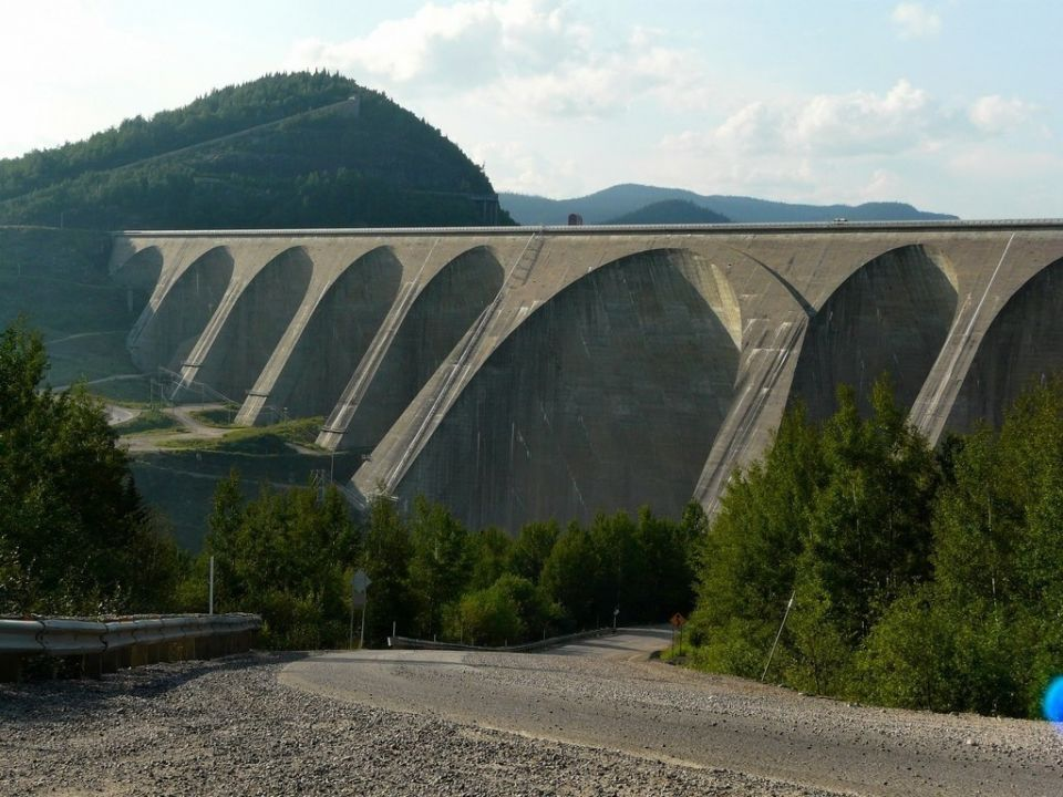 Шедевр гидротехники - плотина Дэниэл-Джонсон на реке Маникуаган (Канада)Есть плотины, которые поражают воображение не столько своими размерами, сколько необычайностью и смелостью конструкции. Особое место среди них занимают так называемые многоарочные плотины. Подлинным шедевром среди них считается канадская ГЭС Маникуаган-5.ГЭС Маникуаган-5 расположена в Канаде, в Квебеке, на реке Маникуаган. Эта река давно привлекала гидроэнергетиков: хорошие расходы и падения, возможность создания в верховьях крупного регулирующего водохранилища. Использовать гидроэнергетический потенциал реки решили каскадом ГЭС. Строительство начали в 1959 году с самой верхней и самой мощной ступени — Маникуаган-5. В 1968 году строительство плотины было в целом завершено, ГЭС достроили к 1971 году.Главной изюминкой проекта является сама плотина. Она контрфорсная многоарочная — т.е. состоит как-бы из нескольких небольших арочных плотин, соединенных друг с другом, и передающих усилия не в берега, как обычная арочная плотина, а на основание через контрфорсы. Плотины такой конструкции требуют наименьшего расхода бетона, но технологически достаточно сложны; сооружение многоарочной плотины требует высокой культуры строительства.Плотина ГЭС Маникуаган-5 (кстати, у плотины есть собственное имя — плотина Дэниэл-Джонсон, в честь премьер-министра Канады, инициировавшего ее строительство) является крупнейшей многоарочной плотиной в мире. Ее высота — 214 м, длина — 1314 м, объем бетона — 2,2 млн.м3. Плотина имеет 14 контрфорсов, которые образуют 13 арок разных размеров, самая крупная из которых, шириной 160 м, находится в центре. Плотина построена из высококачественного морозостойкого бетона, со стороны водохранилища ее поверхность покрыта асфальтом.Плотина образует крупное водохранилище Маникуаган совершенно уникальной — кольцеобразной формы. Столь своеобразный вид водохранилища объясняется его размещением в воронке огромного древнего метеоритного кратера (образовался в результате падения астероида 214 млн