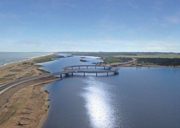 Необычный автомобильный мост в форме кольца совсем недавно построили в Уругвае над лагуной Гарсон. Мост соединяет округа Роха и Мальдонадо на южном побережье.Разработчик проекта, Рафаэль Виньоли, объясняет свою концепцию так: во-первых, въезжая на мост, водителям придется снизить скорость, что обеспечит более безопасное движение, а во-вторых, пассажиры, среди которых немало туристов, смогут лучше рассмотреть красивые природные ландшафты, раскинувшиеся вокруг.
