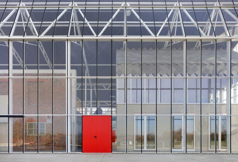 Реконструкция фруктовой фермы в БельгииВ бельгийской деревне Гуик выполнена реконструкция бывшей фруктовой фермы по проекту архитектурного бюро Jo Taillieu Architecten в туристический и образовательный центр Paddenbroek. Несколько сохранившихся сельскохозяйственных зданий заключены в стеклянную теплицу, вместе с дворовой территорией. Проект направлен на развитие сельского туризма, а реконструированный комплекс служит для ознакомления посетителей с региональной историей и идентичностью.Исторические фермерские постройки преобразованы в офисы и залы для проведения встреч, а придомовые территории – в места для проведения выставок и семинаров. Объем из стекла, накрывающий весь комплекс, позволяет очень гибко использовать вновь образованное закрытое пространство. При этом стеклянная крыша теплицы частично покрыта солнечными панелями, которые не только вырабатывают электроэнергию, но и закрывают внутреннее пространство от прямых солнечных лучей.По мнению архитекторов, подобное наслоение старых каменных и новых технологичных конструкций, имеет свое очарование, и как нельзя лучше подходит для объектов такого типа.#реконструкция #теплицы #бельгия