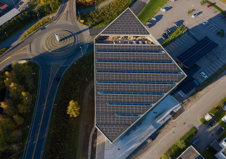 Новый «пассивный» офис «Powerhouse Telemark» возведен по проекту Snøhetta в НорвегииНорвежское архитектурное бюро Snøhetta продолжает реализацию серии энергоэффективных офисных зданий «Powerhouse» («электростанция»). В настоящее время завершено строительство четвертого по счету здания, которое получило название «Powerhouse Telemark» и расположено в административном регионе Телемарк (восточная Норвегия). По сравнению с аналогичным зданием «традиционной» конструкции, потребление энергии снижено на 70%, а с учетом использования альтернативных источников энергии, таких как солнечные панели и геотермальные насосы, здание производит больше энергии, чем потребляет. Отсюда, собственно, и общее название серии – «электростанция».С трех сторон офисное здание защищено деревянными балясинами, затеняющими фасады, наиболее подверженные воздействию солнечных лучей. Под деревянными балясинами здание облицовано фиброцементными фасадными панелями «Cembrit», которые придают зданию единый вид, а также имеют свойство накапливать тепло днем и излучать его ночью. Для отопления используется водяной контур, запитанный от геотермального источника - скважины глубиной 350 метров.Как и остальные здания этой серии, «Powerhouse Telemark» имеет узнаваемый скошенный под 45° объем. Такая форма определена наиболее эффективным углом расположения солнечных панелей. В условиях Норвегии, где световой день крайне ограничен, добиться хорошего эффекта от солнечных панелей достаточно непросто, однако путем моделирования разработчикам проекта удалось достичь выработки электроэнергии в количестве, достаточном не только для собственных нужд, но и для нужд окружающих зданий.#энергоэффективность #общественныездания #норвегия