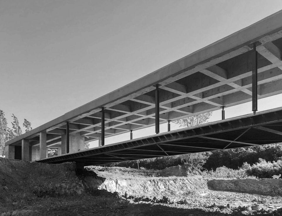 Здание-мост в КитаеВ Вэйхай (Китай) возведено здание-мост выставочного зала по проекту SpaceStation. Сооружение площадью 500 м2 имеет пролет 42 м. В основе пролетной конструкции - стальные балки, скрытые внутри железобетона. На пилоны сечением 1,2х2,5 м, установленные по обе стороны оврага, опираются основные балки шириной 0,6 м и высотой 2,2м, а перпендикулярно к ним располагаются вторичные.К этой системе балок подвешена стальная конструкция павильона – подвесы и рама пола. Преимуществом такой системы, по мнению авторов проекта, является то, что все инженерные коммуникации (электрика, освещение, воздуховоды и трубопроводы) остаются скрытыми внутри верхней системы балок, оставляя открытое и пустое пространство для зала.Панорамное остекление пролетного сооружения подчеркивает его прозрачность и открытость. Визуальную легкость конструкции добавляет и отделка фасада из перфорированного алюминия.#мосты