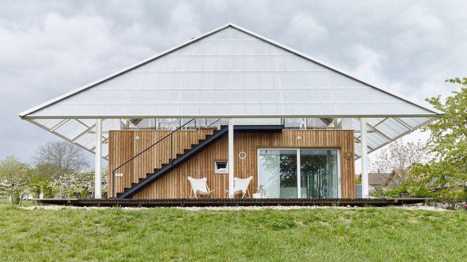 Дом с теплицей на крышеНеобычный частный одноэтажный дом с теплицей на крыше построен в городе Хлум, Чешская республика, по проекту архитектурной студии RicharDavidArchitekti.Здание выполнено в железобетонном каркасе с каменными стенами, облицованными лиственницей и накрыто второй крышей из поликарбоната. Крыша имеет больший размер, чем здание. По периметру организована крытая терраса, с которой имеется доступ в любую из комнат.#малоэтажноестроительство #теплицы
