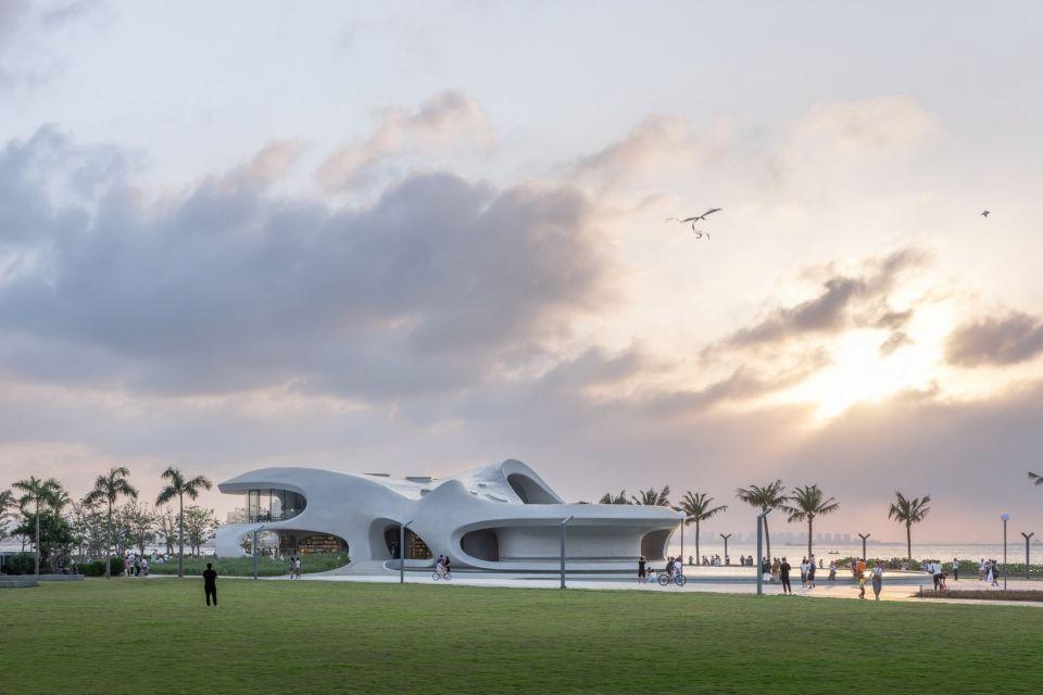 """""""Библиотека червоточин"""" - аморфное здание в КитаеЗдание новой библиотеки, возведенное в Хайкоу (Китай) по проекту MAD Architects, больше всего напоминает облако. Библиотека общей площадью 1000 квадратных метров - первое из шестнадцати зданий, строящихся в парке Century на побережье залива Хайкоу. Все шестнадцать объектов проектируют различные архитектурные компании.Здание с текучей, аморфной формой, выполнено из железобетона , а его фасады и интерьеры напоминают стенки сосуда и не имеют прямых углов. Опалубка сложной формы изготовлена по технологии 3D-печати. Оконные проемы представляют собой бесформенные """"дыры"""", из которых открывается вид на море и через которые в помещения и залы проникает достаточное количество солнечного света.Руководитель бюро MAD, Ма Янсун, считает, что в этом проекте, как ни в каком другом проекте MAD архитектурные акценты смещены в сторону искусства. Здание получилось достаточно скульптурным и разработчики надеются, что оно станет излюбленным местом времяпровождения горожан.Центральное фойе разделяет здание на несколько частей: приемную с офисом, библиотеку, читальный зал и игровую зону для детей. На крыше расположена небольшая терраса.#общественныездания #библиотеки #китай"""