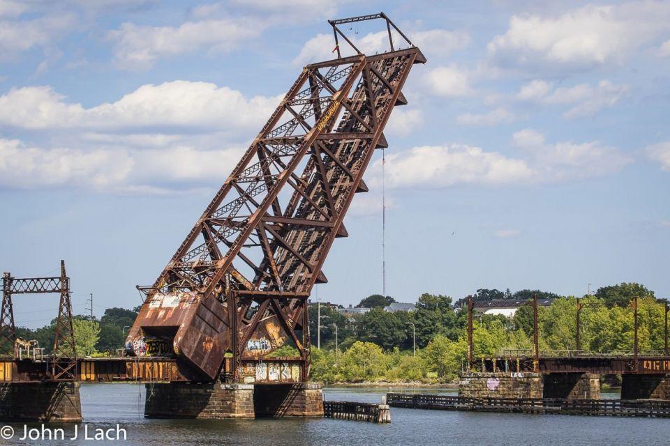 """The Crook Point Bascule Bridge - история """"торчащего"""" мостаРжавый железнодорожный мост Crook Point Bascule Bridge, известный также как """"торчащий мост"""", - самое известное сооружение в Провиденсе (США) и считается чем-то вроде местной иконы архитектуры.Стальной мост с подъемной секцией пролетом 40 м возведен в 1908 году по проекту Scherzer Rolling Lift Bridge Company of Chicago в рамках развития железнодорожной ветки """"New York, New Haven and Hartford Railroad"""" и долгое время использовался для грузовых железнодорожных перевозок через реку Сиконк.С началом промышленного упадка в регионе в 1970х годах, железная дорога практически перестала использоваться и эксплуатировать сложную механику подъемного моста стало слишком накладно. По решению властей, в 1976 году центральная секция была навсегда зафиксирована в положении подъема на 64 градуса, превратившись в некое подобие памятника ушедшей эпохе.Несмотря на брутальный внешний вид, конструкции моста находятся в рабочем состоянии. Сооружение считается безопасным и каждые два года проходит экспертную оценку технического состояния. Сейчас это популярное место сбора и общения неформальной молодежи города.Дальнейшая судьба моста пока не ясна. С одной стороны, он включен в долгосрочный перечень демонтажа (примерный срок 2026-2027 годы), а с другой стороны власти города не теряют надежду превратить сооружение в настоящий арт-объект. С этой целью в 2021 году планируется провести конкурс на лучший проект реконструкции """"торчащего моста"""".#история #мосты #сша"""