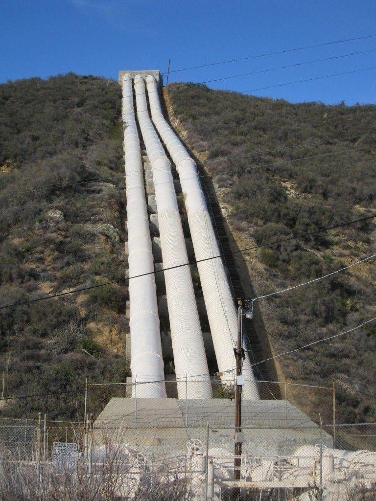 История водоснабжения Лос АнджелесаДля того чтобы нормально функционировать и расти, городу в первую очередь нужна вода, а Лос-Анджелес с трех сторон окружают пустыни, с четвертой — соленый океан. Большие реки — Колорадо и Керн, протекают слишком далеко. Ближайшая, река Оуэнс, — в 360 км к северо-востоку от города, в предгорьях Сьерра-Невады. Собственная же река — Лос-Анджелес, наполняется лишь в редкие периоды дождей, а все остальное время представляет собой начисто пересохшее, заросшее кустарником русло.Решать задачу водоснабжения города в начале 20 столетия довелось уже известному в то время инженеру-самородку Уильяму Малхолланду, выходцу из Ирландии.Откуда брать воду для Лос-Анджелеса, выбирать особенно не приходилось, и все усилия сконцентрировались на реке Оуэнс. Операция эта с самого начала базировалась на обмане, подкупах и финансовых аферах, поскольку на заре XX века Оуэнская долина была заселена фермерами, хозяйства которых процветали, принося хорошие прибыли и многообещающие перспективы. У фермеров долины к тому времени уже имелся свой собственный ирригационный проект. Легальным путем отобрать у фермерской общины воду и закрыть принятый к разработке проект было невозможно. В итоге был получен доступ к закрытым документам земельной описи Оуэнсской Долины и часть ферм вдоль будущей трассы акведука была выкуплена.Сооружение акведука протяженностью в 360 км длилось шесть лет. В строительных работах было задействовано 5 тысяч рабочих, новейшая техника и 6 тысяч мулов. Если выходила из строя техника, ее заменяли мулами. Если гибли люди, нанимались новые.Для нужд строительства был построен огромный цементный комбинат и две мощные электростанции. Прокладывая дорогу акведуку, рабочие пробили 140 туннелей, общей протяженностью 83 км, проложили вдоль водной трассы почти 200 км железнодорожных путей, 800 км шоссейных дорог, протянули 270 км линий электропередач и 385 км телефонных линий. Вода перебрасывалась из реки и озера Оуэн частично по бетонным желобам или канал