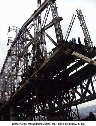 История строительства первого железнодорожного моста через ЕнисейЦентральная Россия второй половины ХIХ века стремительно покрывалась сетью железных дорог. Одним из грандиозных сооружений того времени стал железнодорожный мост через Енисей в Красноярске, возведенный под руководством инженера Евгения Кнорре по проекту профессора Лавра Проскурякова.Строительство моста было начато в 1895, а завершилось в 1899 году. В рамках испытания моста, на него в начале загнали два поезда, каждый из которых состоял из четырёх паровозов и шести вагонов, нагруженных рельсами, а затем по нему прошли два поезда с 23 платформами, груженными рельсами на скорости 70 км/ч .Особенностями сооружения стали: самая большая в России того времени длина моста (907 метров) и самый большой пролёт ферм (144,5 метров). Конструкции ферм выглядели необычайно изящными для таких сооружений. Высота ферм в вершине параболы составляла 20 метров.На этом объекте Кнорре разработал и внедрил сразу несколько инноваций, среди которых был метод сборки больших ферм на берегу с последующей продольной надвижкой на опоры. Передвигали их при помощи точеных цилиндрических роликов, заложенных между рельсовыми путями.Соединение металлических конструкций осуществлялось на заклепках. При этом, заклепки изготавливали по месту, в кузнях на берегу, и тут же, пока они не остыли, вставляли в отверстия конструкций с последующей расклепкой.Непростой задачей было и сооружение опор моста в глубокой части реки. Металл для изготовления кессонов приходил с Урала с большим опозданием, и, чтобы не тормозить работу, Кнорре стал изготавливать кессоны из дерева (этот тип кессона успешно применялся впоследствии при сооружении и других мостов Сибирского пути, в том числе 4-километрового моста через Амур).Непосредственно на сооружении моста работало более двух тысяч человек, а вместе с помощниками их число достигало десяти тысяч. Значительным мост вышел и по своей цене – 3 млн. царских рублей (в традиционной для России манере, это пересичтывало