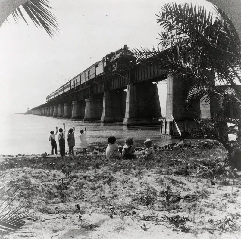 История морской железной дороги Генри ФлаглераОстрова Флорида-Кис связаны с полуостровом Флорида поистине уникальным шоссе – это Overseas Highway, длина которого около 180 километров. Раньше на этом месте была железная дорога, которую в начале ХХ века построил Генри Флаглер.В те времена строительство железной дороги, проходящей через океан потребовало значительных инженерных инноваций, а также привлечения больших объёмов трудового и денежного капиталов. В строительстве было задействовано 4 000 человек. В течение семи лет строительства 5 раз ураганы угрожали сорвать проект, а три из них вызвали значительный урон и привели к гибели людей. Стоимость проекта составила более 27.127.205 долларов, или около 212000 долларов за милю. При строительстве погибло около 200 человек. Несмотря на все трудности, последнее звено Восточной железной дороги Флориды было завершено к 1912 году.В ходе строительства было использовано 38000 тонн металлоконструкций, 461 000 кубических ярдов бетона (350 000 м³), 800000 баррелей цемента, 96 000 тонн гранита, 78000 гравия, 300000 тонн коралловых пород; формирование насыпей потребовало около 100 000 тонн грунта.Общая длина железной дороги составила 248 километров, из них 70 километров проходили по 47 островам Мексиканского залива. Из 106 миль (170 км) маршрута от бухты Джевфиш до Ки-Уэст 37 (59 км) проходило по открытому морю. Около 20 миль (32 км) линии было построено на искусственных насыпях, 17 миль (27 км) — на бетонных и железобетонных мостах. Из 38 мостов 29 были бетонными, 6 железобетонными и 3 разводными (четвёртый разводной мост в проливе Indian Key был разобран).21 января 1912 года по железной дороге отправился первый поезд, на котором Генри Флаглер проехал в своём личном вагоне, знаменуя завершение строительства железной дороги в Ки-Уэст, куда прибыл 22 января; таким образом, все восточное побережье Флориды было связано посредством железных дорог. Морская железная дорога была широко известна как «Восьмое чудо света»Морская железная дор