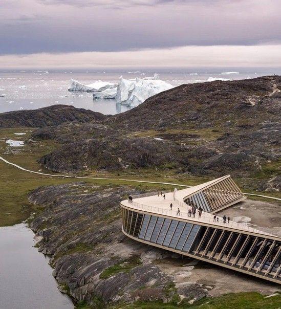 Центр климатических исследований в ГренландииНовый центр климатических исследований расположен в Гренландии, в 250 километрах от Полярного Круга. Комплекс возведен в 2021 году по проекту датской архитектурной студии Dorte Mandrup для отслеживания последствий изменения климата в этом регионе, а также для проведения выставок и образовательных мероприятий. В центре работают кинотеатр и кафе.Здание закрученной треугольной формы спроектировано так, чтобы выглядеть легким и незначительным на фоне колоссального масштаба арктической дикой природы, так, чтобы посетители могли по-настоящему раствориться в ней. А наблюдать в этом месте действительно есть что: океан, айсберги, полуночное солнце и северное сияние открываются здесь во всей красе.Чтобы нанести минимум вреда окружающей среде, проектировщики старались ограничить использование бетона, отдав предпочтение легкому стальному каркасу на сваях. Поэтому, большая часть пространства под зданием осталось нетронутым.Одна из сторон изогнутой крыши доходит до уровня земли, позволяя посетителям подняться на обзорную площадку с видом на дрейфующие айсберги фьорда Кангиа. Помещения центра также имеют панорамное остекление, обеспечивающее великолепный обзор окрестностей.#общественныездания #гренландия
