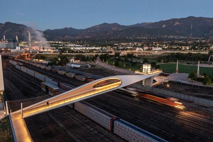 """""""Скульптурный"""" пешеходный путепровод в СШАПутепровод Park Union Bridge со скульптурными вырезами возведен в Колорадо Спрингс (США) в районе комплексов Олимпийского и Паралимпийского музеев по проекту Diller Scofidio + Renfro. Сооружение пролетом порядка 80 м, переменной шириной 5-7 м и высотой 7,6 м, выполнено из стальных конструкций и отделано композитными панелями. Настил моста железобетонный. Общая масса сооружения составляет - 500 тонн. Стоимость проекта - 20 миллионов долларов.Сооружение предназначено для передвижения пешеходов и велосипедистов через пути грузовой железнодорожной станции.Однако по мнению местных жителей новое сооружение для них стало не просто способом пересечь железную дорогу, а местной достопримечательностью, наряду с объектами олимпийского комплекса. Необычная форма и изогнутые линии моста гармонируют с контекстом Скалистых гор. В вечернее время конструкции моста эффектно подсвечиваются.#мосты #сша"""
