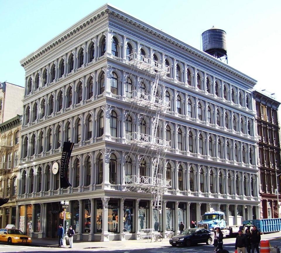 """История """"чугунной архитектуры"""" Нью-ЙоркаНесущие и декоративные конструкции из чугуна для небольших зданий начали использоваться в Нью-Йорке еще в самом начале XIX века, но расцвет """"чугунной"""" архитектуры (cast iron architecture) пришелся на его середину и конец.Преимущества чугунных конструкций - тиражируемость и высокая скорость сборки. По одной форме за пару дней можно было отлить несколько десятков деталей. К середине позапрошлого века здания стали делать на чугунно-литейных заводах и собирать на месте, как конструктор. И пока консервативные владельцы частных особняков размышляли над преимуществами нового материала, чугун уверенно вошел в промышленную архитектуру, придав новым офисам и фабрикам ажурный и даже парадный вид.Сложные капители, декоративные карнизы, тонкие изящные колонны просто прикручивались на болтах к фасаду и красились «под каменные». Так в Нью-Йорке появились сборные фасады, а потом и целые дома, собранные из чугуна. Многоэтажные, просторные, наполненные светом фабричные, офисные и коммерческие палаццо стали новым лицом развивающегося города.Так появились район текстильных мануфактур Сохо (SoHo), улица больших и роскошных универмагов в Челси, коммерческие кварталы Трайбеки. Здесь были здания, копирующие знаменитые венецианские палаццо, пышный стиль Второй империи, османовские мансарды и мавританские дворцы, не обошлось и без влияния только появившейся моды на ар-нуво.После Второй мировой войны промышленность ушла из города и некогда богатые чугунные кварталы опустели. Их ждала бы участь большинства заброшенных промышленных районов - снос, если бы не нью-йоркская богема. Опустевшие офисы и фабрики заняли художники, а в 1962 году было создано «Общество друзей чугунной архитектуры». Еще через пару лет район получил статус исторического памятника - SoHo Cast Iron Historic District и в течение следующей дюжины лет превратился в модный художественный район.Сегодня в Нью-Йорке сохранилось более 250 «чугунных» зданий, построенных на протяжение XIX века, """