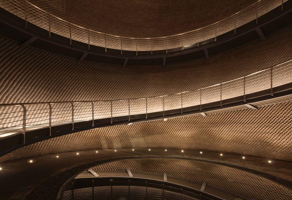 """Эрлангский ликеро-водочный склад поместья ЛанцзюПроект этого склада - победитель конкурса ArchDaily """"Building of the year 2021"""" в области промышленной архитектуры. Ликеро-водочный складской комплекс возведен в 2018 году в предместье города Эрланг (Сычуань, Китай) по проекту архитектурных бюро """"Langjiu Group"""" и """"DCA"""".Назначение склада - хранение ликера в традиционных глиняных кувшинах. Однако, как и у большинства современных винных и ликеро-водочных заводов, у него есть и второе назначение. Современные предприятия такого типа - это культурные и туристические центры, места для проведения экскурсий, знакомства с историей производства напитка и промышленной историей региона.В своем проекте архитекторы пересмотрели образ промышленного здания, отступив от стереотипов и придав ему выразительность, соответствующую окружающей застройке и природному ландшафту. По их мнению , терракотовый кирпич, из которого выполнены стены, имеет неотъемлемую связь с глиняным сосудом, поскольку они произведены из одного и того же материала. Земляной цвет и узор кирпичного фасада как нельзя лучше соответствуют функциональному назначению предприятия.Центральный объект складского комплекса - здание в форме сосуда, выполненное из 150 тысяч терракотовых кирпичей. Его сложная конструкция призвана отражать """"ремесленный дух"""" региона. Окружающие здание бассейны служат не только элементом дизайна, но и выполняют свою роль в поддержании температурно-влажностного режима работы склада: таким образом обеспечивается идеальная среда для хранения ликера естественным и устойчивым способом.#винодельни #каменныеконструкции #китай"""