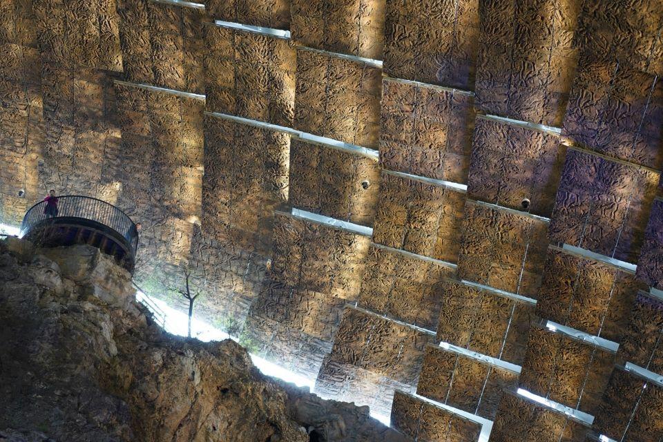 """Укрытие для пещеры """"пекинского человека""""В 2009 году в одной из пещер, являющейся частью грота Чжоукоудяня, расположенного близ Пекина были обнаружены останки древнего человека, возрастом порядка 750000 лет. Кроме этой находки, в пещере хранятся и другие древние окаменелости, обобщенно называемые в научной среде """"пекинским человеком"""".Проект защитного сооружения был реализован в 2018 году после того, как из-за сильного ливня пещеру затопило, и часть артефактов была повреждена. Укрытие спроектированное архитектурно-проектным и научно-исследовательским институтом Университета Цинхуа (THAD), служит для защиты пещеры от дождя и ветра, а также уменьшает колебания температуры и влажности.Конструкция состоит из стального каркаса с двухслойной обшивкой, насчитывающей 825 перекрывающих друг друга панелей. Сооружение накрывает площадь 3700 квадратных метров и в самом широком месте имеет размеры 54х77 метров. Вся конструкция опирается только на два ряда фундаментов, расположенных с севера и юга от пещеры на плоских скальных участках.Форма сооружения смоделирована учеными и воспроизводит ландшафт местности, который здесь был в далекие времена. Наружный слой панелей выполнен из алюминия, и в них предусмотрены места для посадки растений, что должно помочь сооружению слиться с участком.#навесы  #китай"""